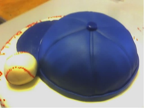 The baseball cap is 9 inches in diameter... and the ball is pretty much to scale.
